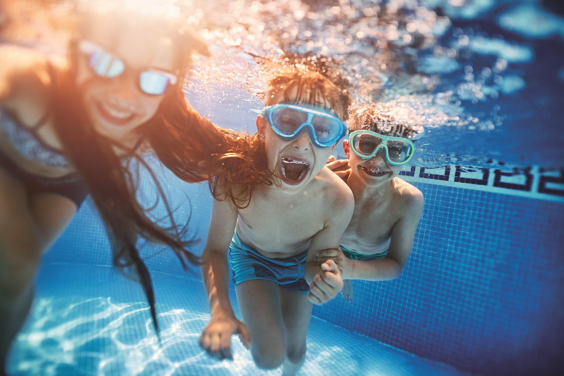 children swimming under water in pool